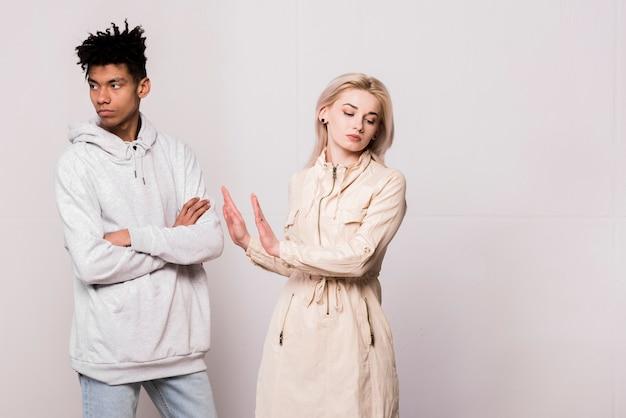 Retrato, de, interracial, par jovem, ignorando, um ao outro, contra, branca, fundo Foto gratuita