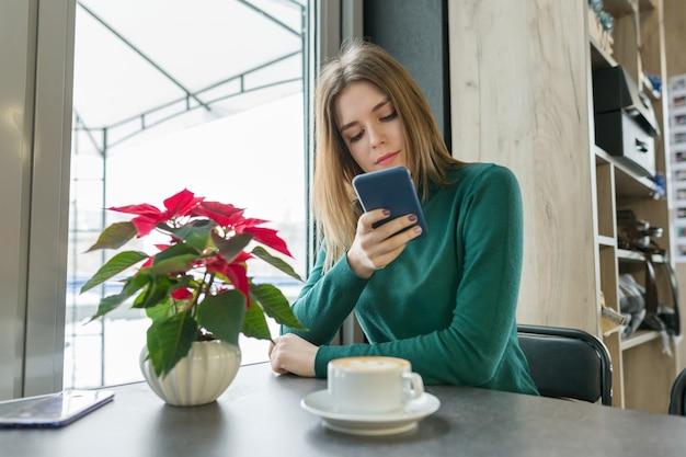 Retrato de inverno da linda jovem sentado no café Foto Premium