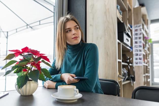Retrato de inverno da mulher sentada no café com uma xícara de café Foto Premium