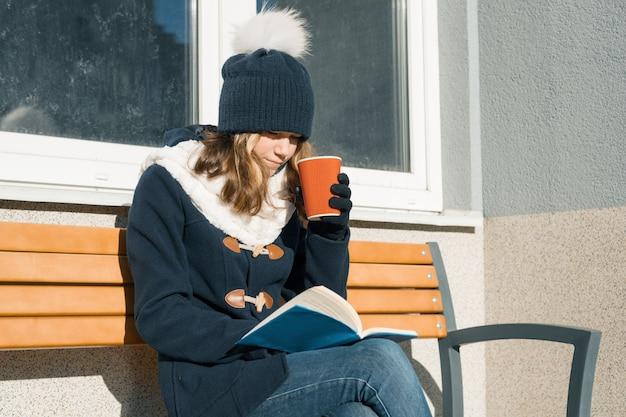 Retrato de inverno de jovem adolescente com copo de bebida quente e livro. Foto Premium