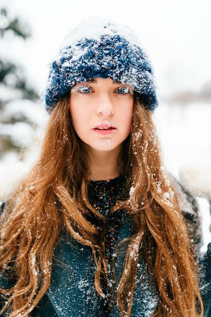 Retrato de inverno de menina morena cabelos longos bonita com o rosto e cabelos cobertos de neve. Foto Premium
