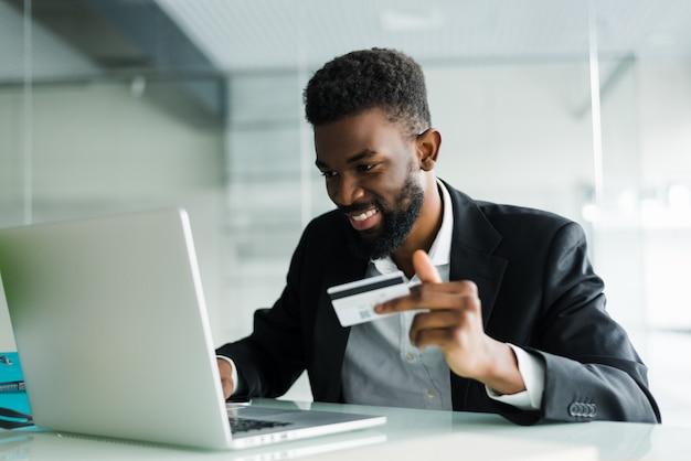 Retrato de jovem africano confiante segurando o cartão de crédito com o laptop pagando via internet Foto gratuita