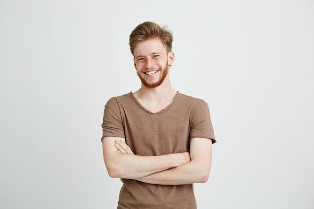 Retrato de jovem alegre feliz com barba sorrindo com braços cruzados. Foto gratuita