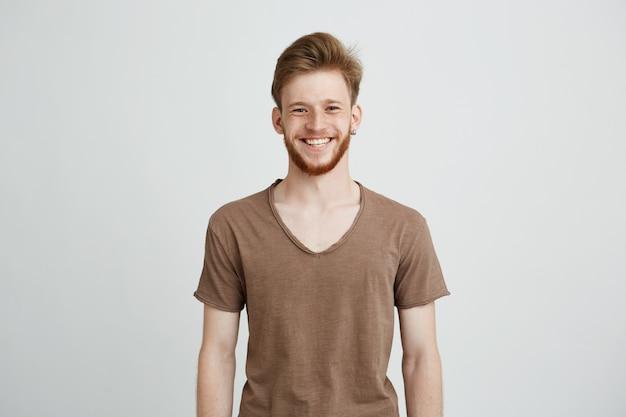 Retrato de jovem alegre feliz com barba sorrindo. Foto gratuita