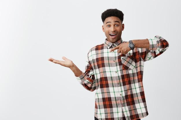 Retrato de jovem alegre pele engraçada cara com penteado afro em camisa casual quadriculada fingindo segurando algo na palma da mão, apontando com a mão com expressão excitada Foto gratuita