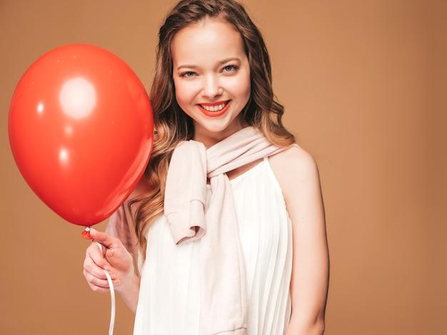 Retrato de jovem animado posando no vestido branco na moda verão. mulher sorridente com balão vermelho posando. modelo pronto para a festa Foto gratuita