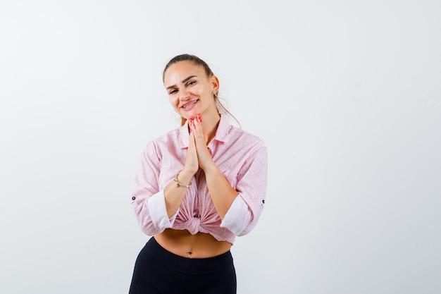 Retrato de jovem apertando as mãos em um gesto de oração na camisa Foto gratuita