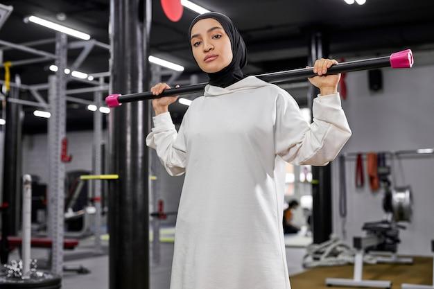 Retrato de jovem árabe se exercitando com pesos na academia, olhando para a câmera, séria e confiante, usando um hijab esportivo branco Foto Premium