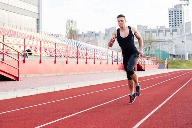 Retrato de jovem atleta masculino de aptidão correndo na pista de corrida no estádio Foto gratuita
