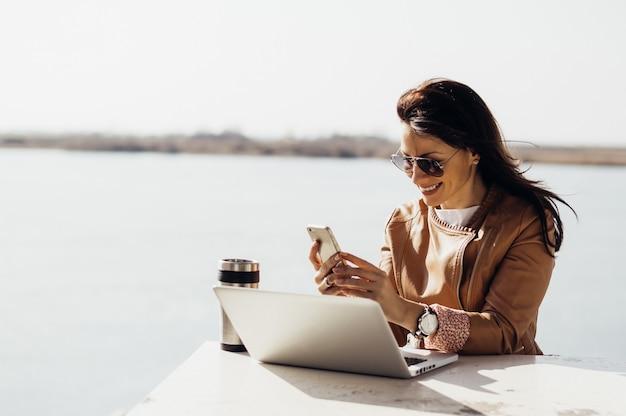Retrato, de, jovem, atraente, executiva, verificar, email, telefone, ao ar livre Foto Premium