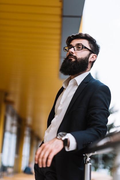 Retrato, de, jovem, barbudo, homem negócios, com, pretas, óculos Foto gratuita