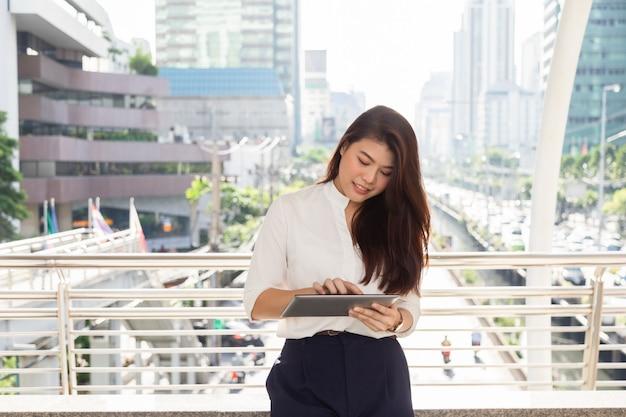 Retrato, de, jovem, bonito, asiático, executiva, desgastar, em, camisa branca, digitando, ligado, taplet Foto Premium