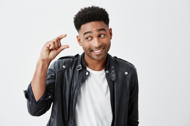 Retrato de jovem bonito homem engraçado de pele escura com penteado afro em camiseta branca e jaqueta de couro gesticulando com a mão, mostrando pouco tamanho, olhando de lado com a expressão do rosto cínico. Foto gratuita