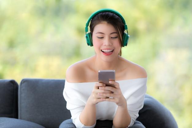 Retrato, de, jovem, bonito, mulher asian, sentar sofá, e, escutar música, com, auscultadores Foto Premium