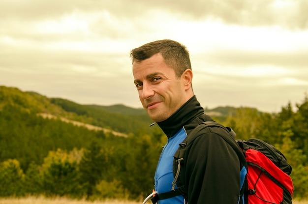 Retrato de jovem bonito na paisagem de montanha verde. retrato do rosto bem sucedido de alpinista Foto Premium