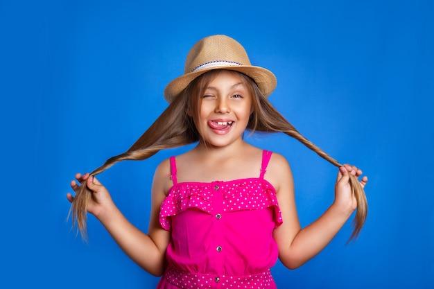 Retrato de jovem bonito no vestido rosa e chapéu se divertindo. férias de verão e o conceito de viagens Foto Premium