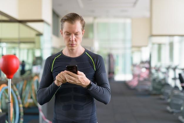 Retrato de jovem bonito usando o telefone na academia durante covid-19 Foto Premium