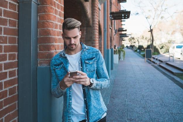 Retrato de jovem bonito usando seu telefone celular ao ar livre na rua. conceito de comunicação. Foto gratuita