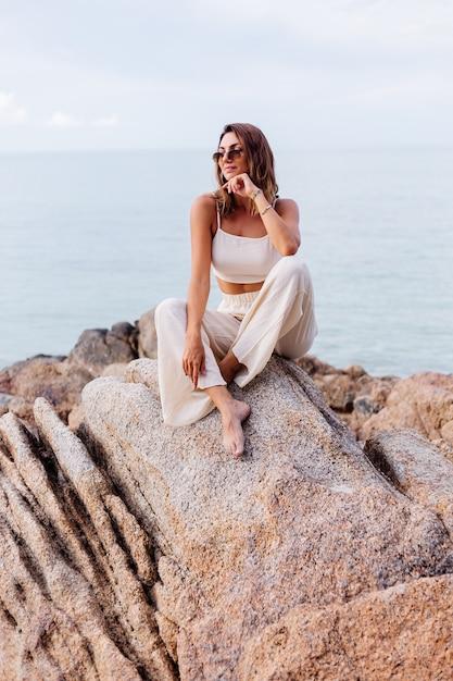 Retrato de jovem calmo, feliz, caucasiano, apto, magro, mulher, corte, cami, top e, calça conjunto, fica, sozinho, em, rochoso, praia Foto gratuita