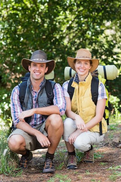 Retrato de jovem casal agachado na floresta Foto Premium