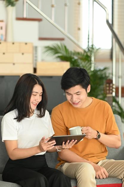 Retrato de jovem casal feliz usando tablet navegando na internet no sofá em casa Foto Premium
