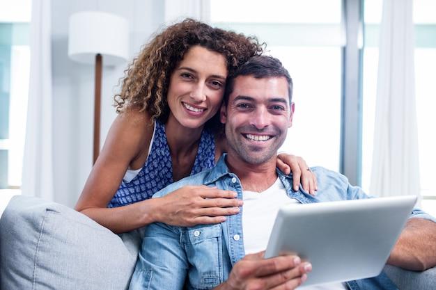 Retrato de jovem casal usando um tablet digital no sofá Foto Premium