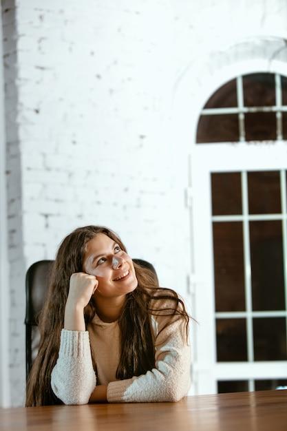 Retrato de jovem caucasiana em roupas casuais parece sonhador, fofo e feliz. olhando para cima e pensando, sentado dentro de casa à mesa de madeira. conceito de futuro, alvo, sonhos, visualização. Foto gratuita