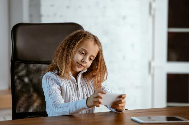 Retrato de jovem caucasiana parece sonhador, fofo e feliz. olhando para cima, sentado dentro de casa à mesa de madeira com tablet e smartphone. conceito de futuro, alvo, sonho de comprar, visualização. Foto gratuita