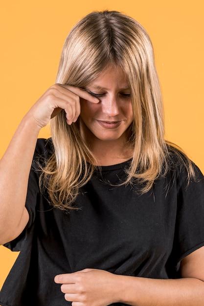 Retrato, de, jovem, chorando, mulher, ficar, frente, parede amarela Foto gratuita