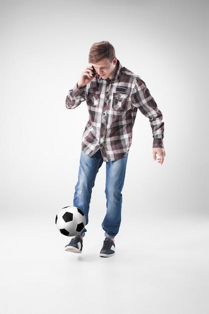 Retrato de jovem com telefone inteligente e bola de futebol Foto gratuita