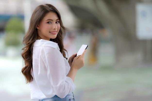 Retrato de jovem com uma carinha sorridente, usando um telefone, caminha por uma cidade Foto Premium