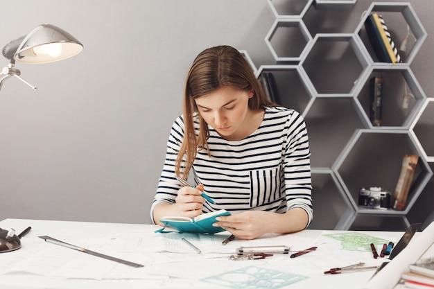 Retrato de jovem concentrado engenheiro freelancer feminino bonito com cabelo escuro em roupas listradas, escrevendo tarefas para amanhã. gerenciamento de tempo. Foto gratuita