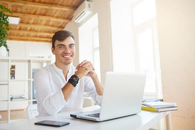 Retrato de jovem empresário de sucesso e feliz usando camisa branca no escritório Foto gratuita
