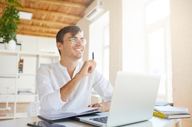 Retrato de jovem empresário feliz e pensativo usando camisa branca no escritório Foto gratuita