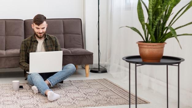Homem jovem trabalhando de casa com computador pessoal e café