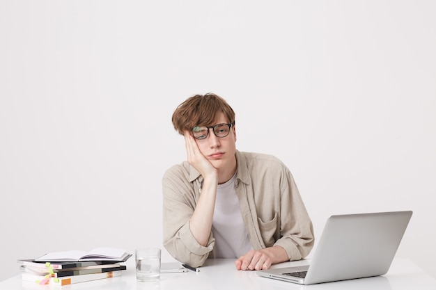 Retrato de jovem espantado estudante vestindo camisa bege parece surpreso e estuda na mesa com o laptop e notebooks isolados sobre a parede branca Foto gratuita
