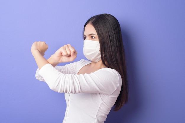 Retrato de jovem está usando máscara facial em fundo roxo Foto Premium