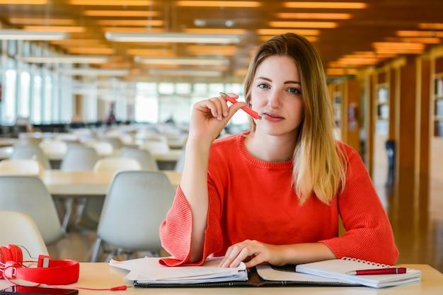 Retrato de jovem estudante estudando na biblioteca da universidade. conceito de educação e estilo de vida. Foto gratuita