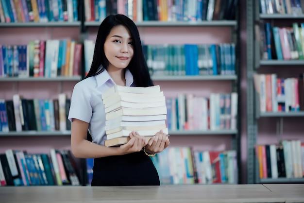 Retrato, de, jovem, estudante, lendo um livro, em, um, biblioteca Foto gratuita