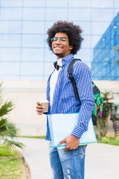 Retrato, de, jovem, estudante masculino, segurando, copo descartável, e, livros, em, mão, ficar, contra, campus Foto gratuita