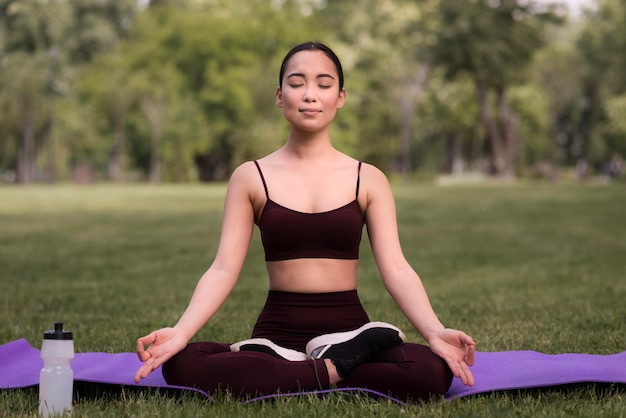 Retrato de jovem exercitando ioga Foto gratuita