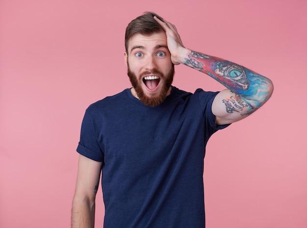Retrato de jovem feliz espantado jovem atraente de barba vermelha, vestindo uma camiseta azul, com a boca escancarada de surpresa, segure a cabeça, ouvi uma notícia muito boa, isolada sobre fundo rosa. Foto gratuita