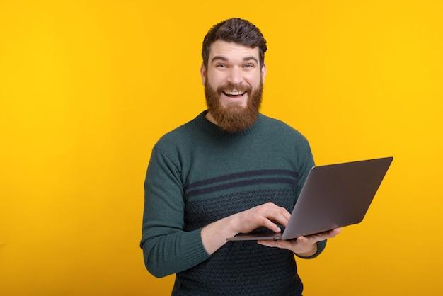 Retrato de jovem feliz usando laptop em pé sobre parede amarela Foto Premium