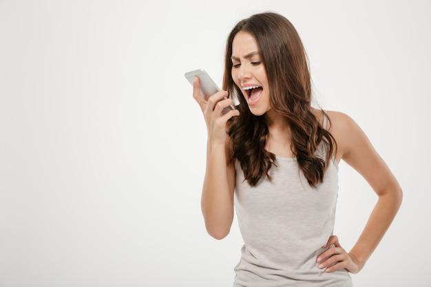 Retrato de jovem gritando no telefone móvel, sendo irritado e com raiva sobre o branco Foto gratuita