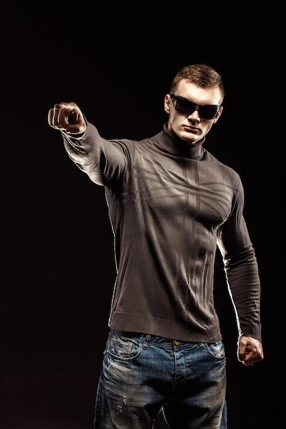 Retrato de jovem homem aponta um dedo isolado na cena negra Foto Premium