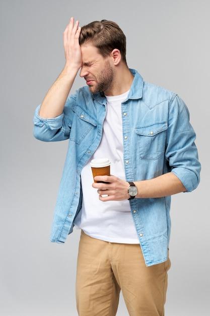 Retrato de jovem homem bonito caucasiano em camisa jeans segurando uma xícara de café para viagem Foto Premium