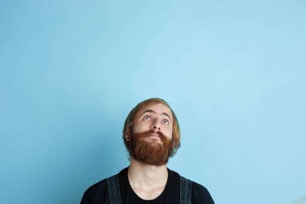 Retrato de jovem homem caucasiano parece sonhador, bonito e feliz. olhando para cima e pensando no espaço azul Foto gratuita