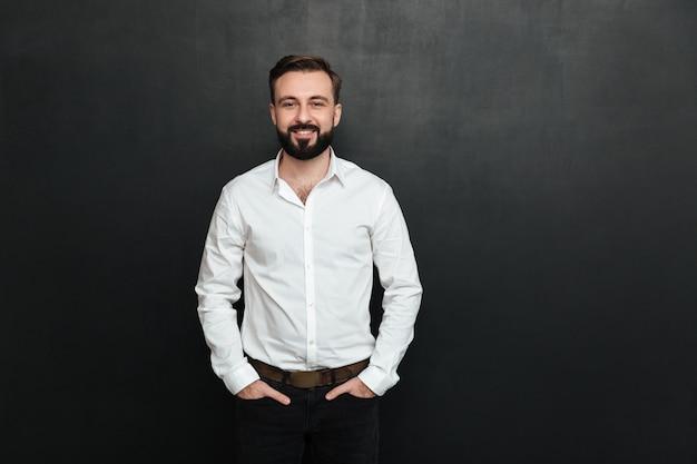 Retrato de jovem homem de camisa branca, posando na câmera com um amplo sorriso e as mãos nos bolsos sobre cinza escuro Foto gratuita