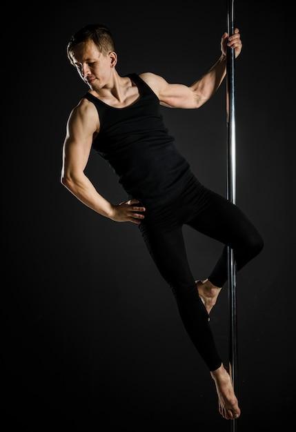 Retrato de jovem homem fazendo uma dança do poste Foto gratuita