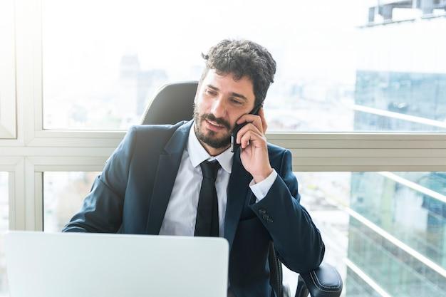 Retrato, de, jovem, homem negócios, falando telefone móvel, perto, a, janela Foto gratuita